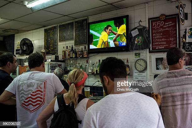 Peole watch on at a local bar as Brazil's soccer sensation Marta Vieira da Silva is shown on tv dejected after losing to Sweden in a penalty shoot...