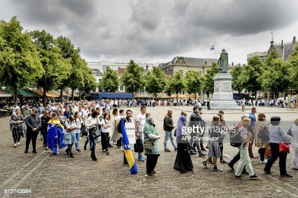 Peolpe attend a commemoration ceremony for the 1995 Srebrenica massacre in The Hague on July 11 2017 Bosnian Serb forces captured the eastern Bosnian...