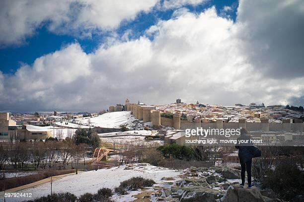 Peolple overlooking Avila town in snow