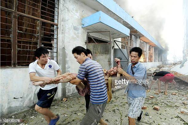 Peope carry a wounded woman from the site of an explosion at a plastics factory in Nanjing east China's Jiangsu province on July 28 2010 At least two...