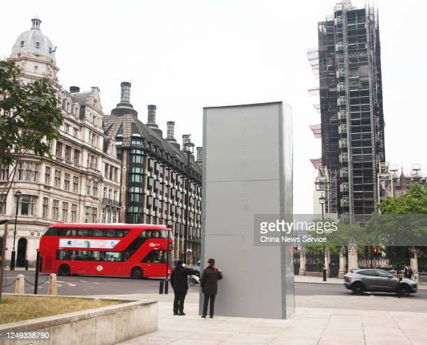 Peope look at the boarded up statue of former British Prime Minister Sir Winston Churchill at Parliament Square ahead of this weekends Black Lives...