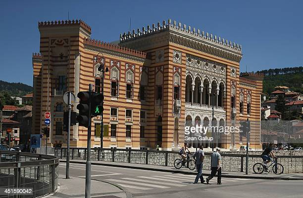 Peope walk past City Hall called the Vijecnica and is the former National Library that was destroyed by Serbian shelling during the 19921995 Bosnian...