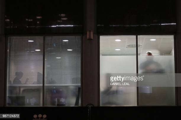TOPSHOT Peopel are seen through blinds searching inside the offices of Cambridge Analytica in central London on the evening of March 23 just hours...