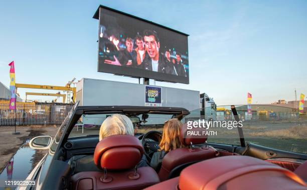 Peopel watch the romantic musical film Grease from their cars at a temporary drive in cinema situated by the iconic Harland and Wolff cranes at...