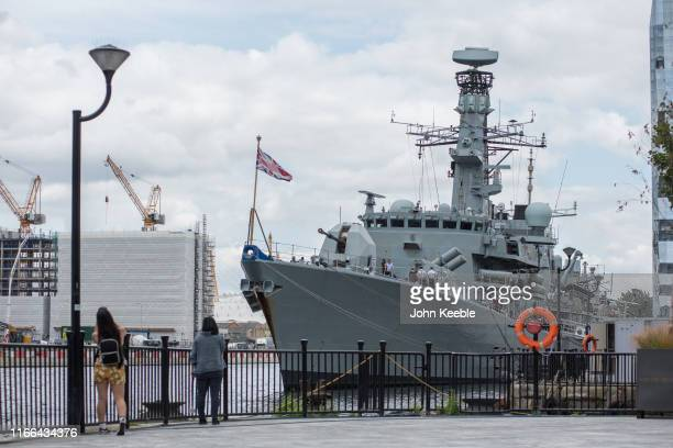 Peopl view the Royal Navy frigate HMS Westminster Type 23 DukeClass antisubmarine ship which is docked at Thames Quay South Dock on the Isle of Dogs...