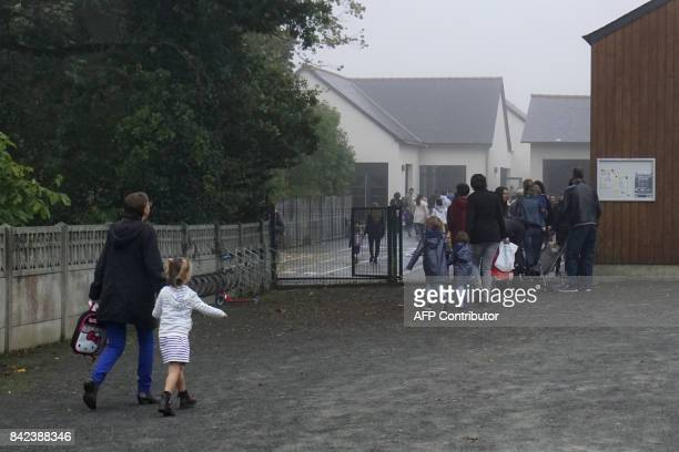 People accompany pupils at a primary school in HedeBazouges western France on September 4 on the first day of the new school year / AFP PHOTO /...