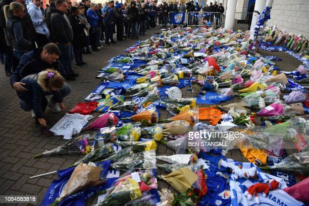 People add flowers to a growing pile of tributes outside Leicester City Football Club's King Power Stadium in Leicester eastern England on October 28...