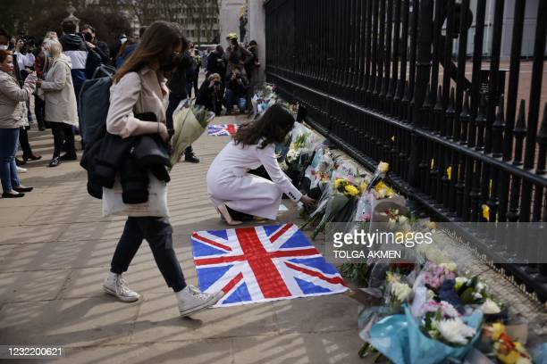 People add flowers to the tributes laid at the railings at the front of Buckingham Palace in central London on April 9, 2021 after the annoucement of...