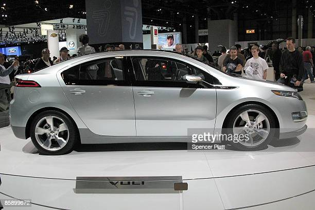 People admire a Chevrolet Volt electric car during the New York Auto Show at Jacob Javits Convention Center on April 10 2009 in New York City Over 1...
