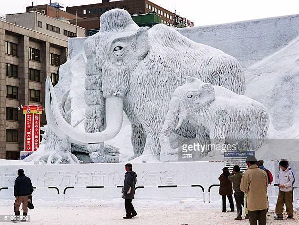 People admire the large snow sculpture of mammoths the scene of Hokkaido which dates back 20000 years at the 50th Sapporo snow festival in Hokkaido...