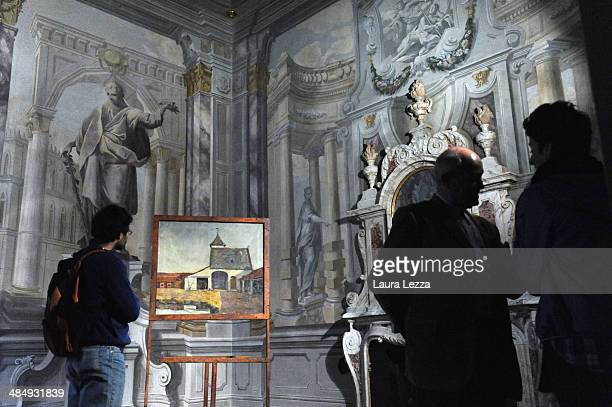 People admire the painting 'The Protestant Barn' ahead of the press conference for the exhibition 'Vincent Van Gogh The enigma of Protestant Barn'...