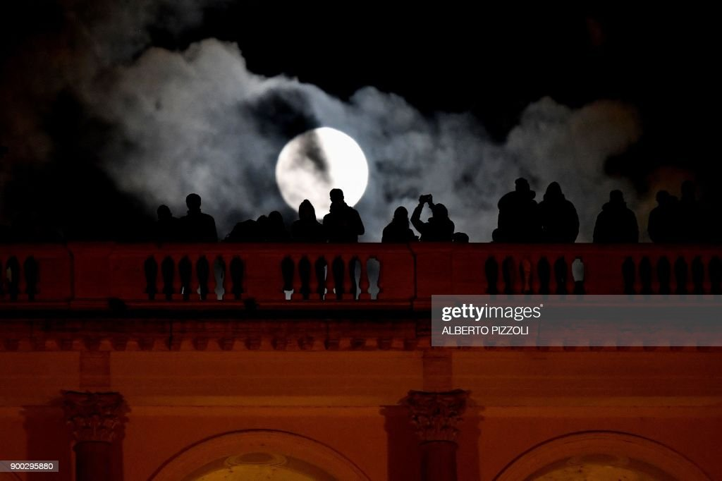 People admires the 'super moon' from the Terrazza del Pincio, in Rome, on January 1, 2018. Supermoons happen when a full moon approximately coincides with the moon's perigee, or a point in its orbit at which it is closest to Earth. This makes the moon appear up to 14 percent larger and 30 percent brighter than usual. / AFP PHOTO / Alberto PIZZOLI