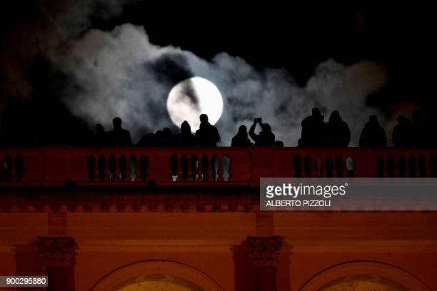 People admires the 'super moon' from the Terrazza del Pincio in Rome on January 1 2018 Supermoons happen when a full moon approximately coincides...