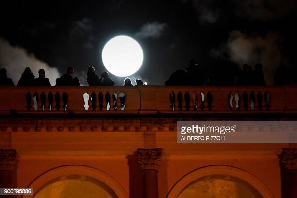 People admires the super moon from the Terrazza del Pincio in Rome on January 1 2018 Supermoons happen when a full moon approximately coincides with...
