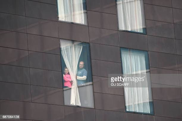 TOPSHOT People affected by the deadly terror attack at Manchester Arena look out from a hotel window in Manchester northwest England on May 23 2017...