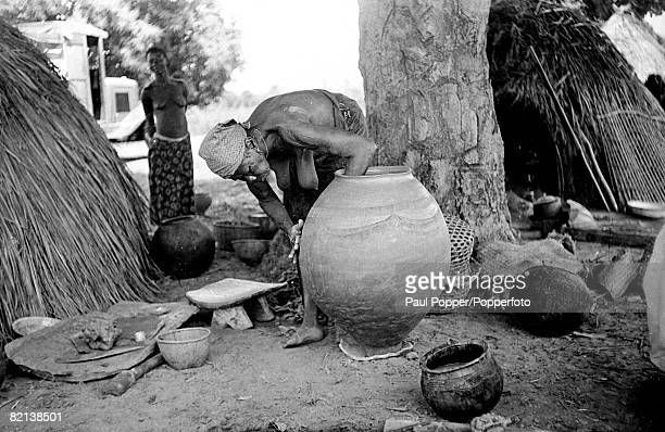 circa 1950's An elderly African woman at work making pots in her village