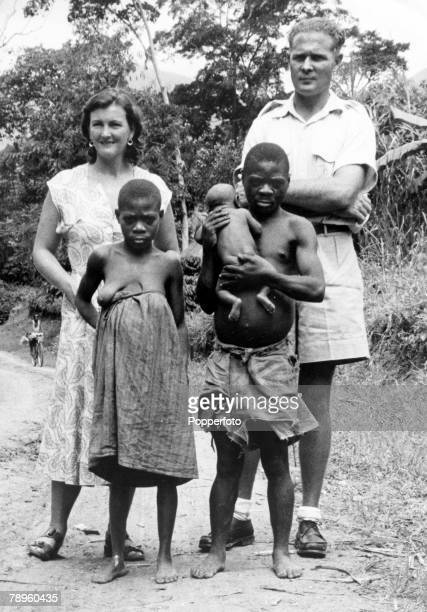 circa 1960 A pygmy family photographed with a European man and woman for comparison
