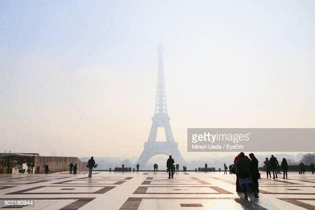 people against eiffel tower during foggy weather - international landmark stock pictures, royalty-free photos & images