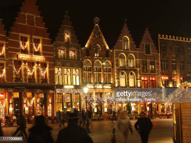 people against illuminated buildings at night during christmas - bruges stock pictures, royalty-free photos & images
