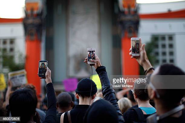 People aim cell phones at a speaker in front of the TCL Chinese Theatre as they march on Hollywood Boulevard to protest of the decision in New York...