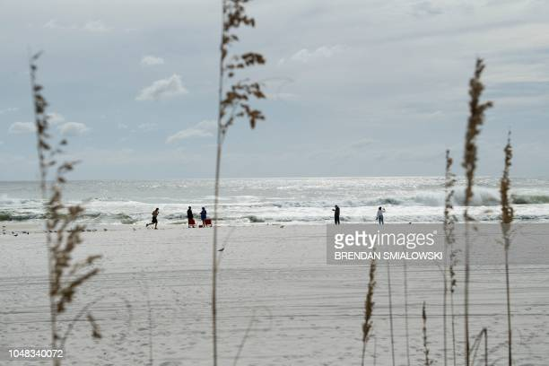 People along the beach with the Gulf of Mexico as Hurricane Michael approaches October 9 2018 in Panama City Beach Florida Hurricane Michael...