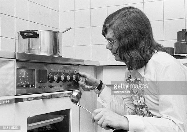 people amateur cook young man crouches with a ladle in front of the cooking stove and regulates the cooking temperature a cooking pot stands on the...