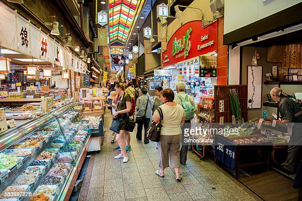 people amidst stalls at nishiki market - nishiki market stock photos and pictures