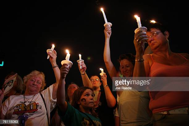 People amongst a crowd of Elvis Presley fans hold candles during a vigil outside the front gates of Graceland Mansion the home of Elvis Presley on...