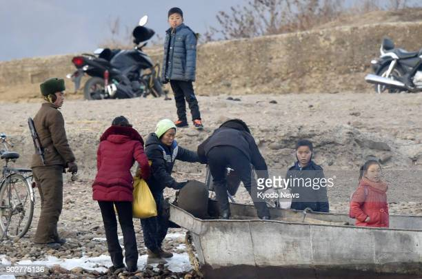People and a boat are seen on the North Korean shore in this photo taken from Dandong a Chinese border city with North Korea on Jan 7 2018 ==Kyodo