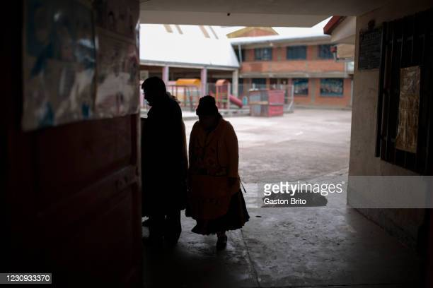 People and a dog are seen at the main door of Unidad educativa 1 de Mayo on February 2, 2021 in El Alto, Bolivia. Despite classes officially started...