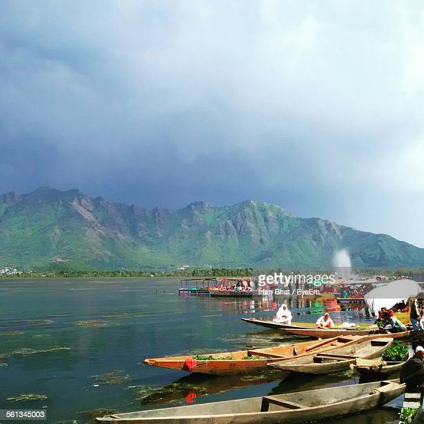 People And Boats At Riverbank Against Cloudy Sky