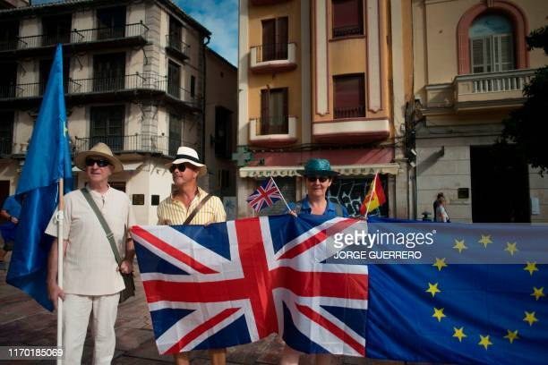 People and British nationals wave an European flag and a British flag as they take part in a protest against Brexit in Malaga on September 22 2019...