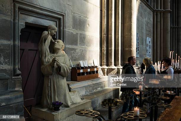 Personas y velas dentro de catedral de Reims, Francia