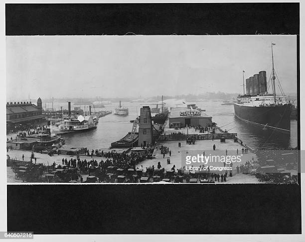 People and carriages line the wharf waiting for the Lusitania to dock ca 1907 New York City