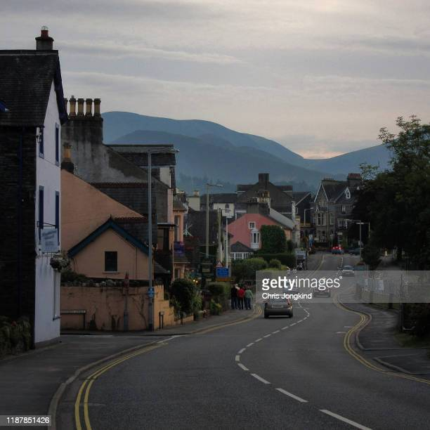 people and cars in a quiet mountain village - keswick stock pictures, royalty-free photos & images