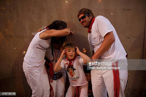 People and children take cover as the 'Toro de Fuego' runs throught the streets during the opening day of the San Fermin Running of the Bulls fiesta...
