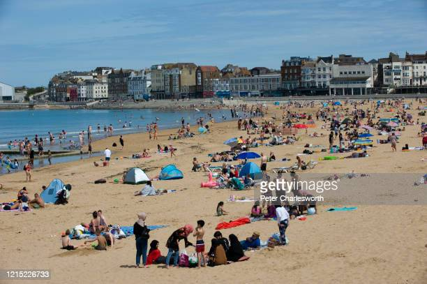 People and families on the beach sunbathing, swimming, playing and generally enjoying the fine sunshine in one of England's oldest seaside resorts,...