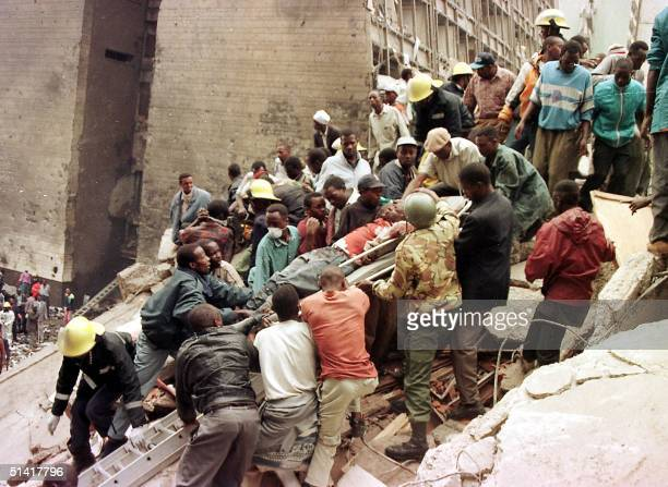 People and firemen work to remove the bodies of people who died when a bomb exploded near the US embassy and a bank in Nairobi 07 August killing at...