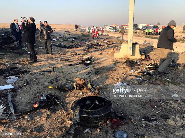 People and journalists are pictured next to the wreckage after a Ukrainian plane carrying 176 passengers crashed near Imam Khomeini airport in the...