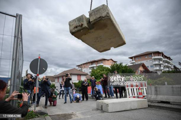 TOPSHOT People and journalists watch a concrete block closing the SwissFrench border removed by Swiss customs on June 14 2020 in Thonex near Ambily...