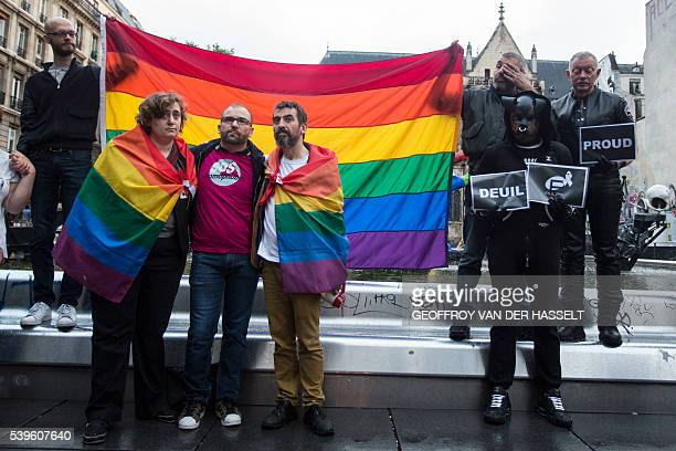 People and members of the gay community holding the peace rainbow flag gather for a vigil near the Beaubourg art center in downtown Paris on June 12...
