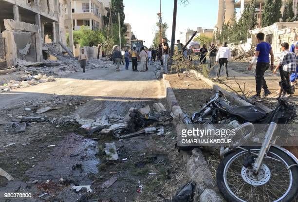 People and members of the Syrian Civil Defence gather at the scene of double explosion in the northern rebelheld city of Idlib on June 21 2018