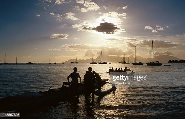People and outrigger canoes at sunset.