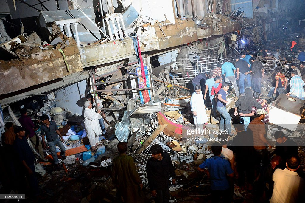 People and Pakistani rescuers work on the site of the bomb blast in Karachi on March 3, 2013. A bomb attack in Pakistan's largest city Karachi on Sunday killed at least 23 people, including women and children, and wounded 50 others, police said. AFP PHOTO/Rizwan TABASSUM