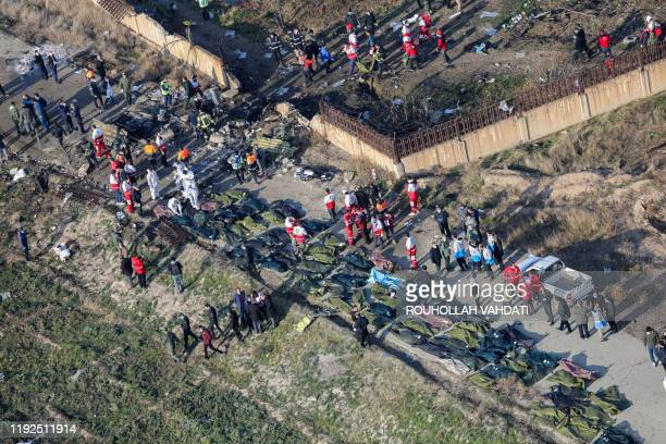 People and rescue teams are pictured amid bodies and debris after a Ukrainian plane carrying 176 passengers crashed near Imam Khomeini airport in the...