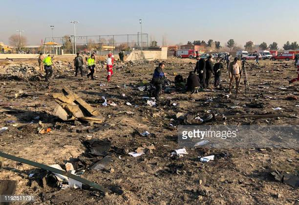 People and rescue teams are pictured amid the wreckage after a Ukrainian plane carrying 176 passengers crashed near Imam Khomeini airport in the...
