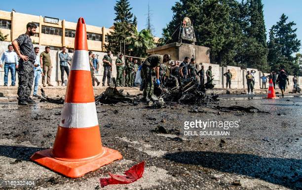 People and security forces gather at the scene of a car bomb explosion in the Kurdishmajority city of Qamishli in northeastern Syria's Hasakeh...