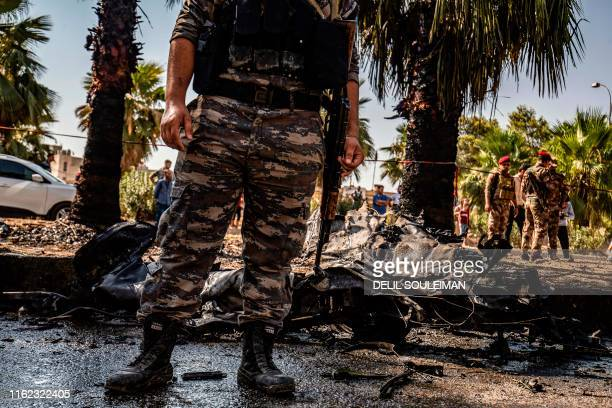 People and security forces gather at the scene of a car bomb explosion in the Kurdish-majority city of Qamishli in northeastern Syria's Hasakeh...