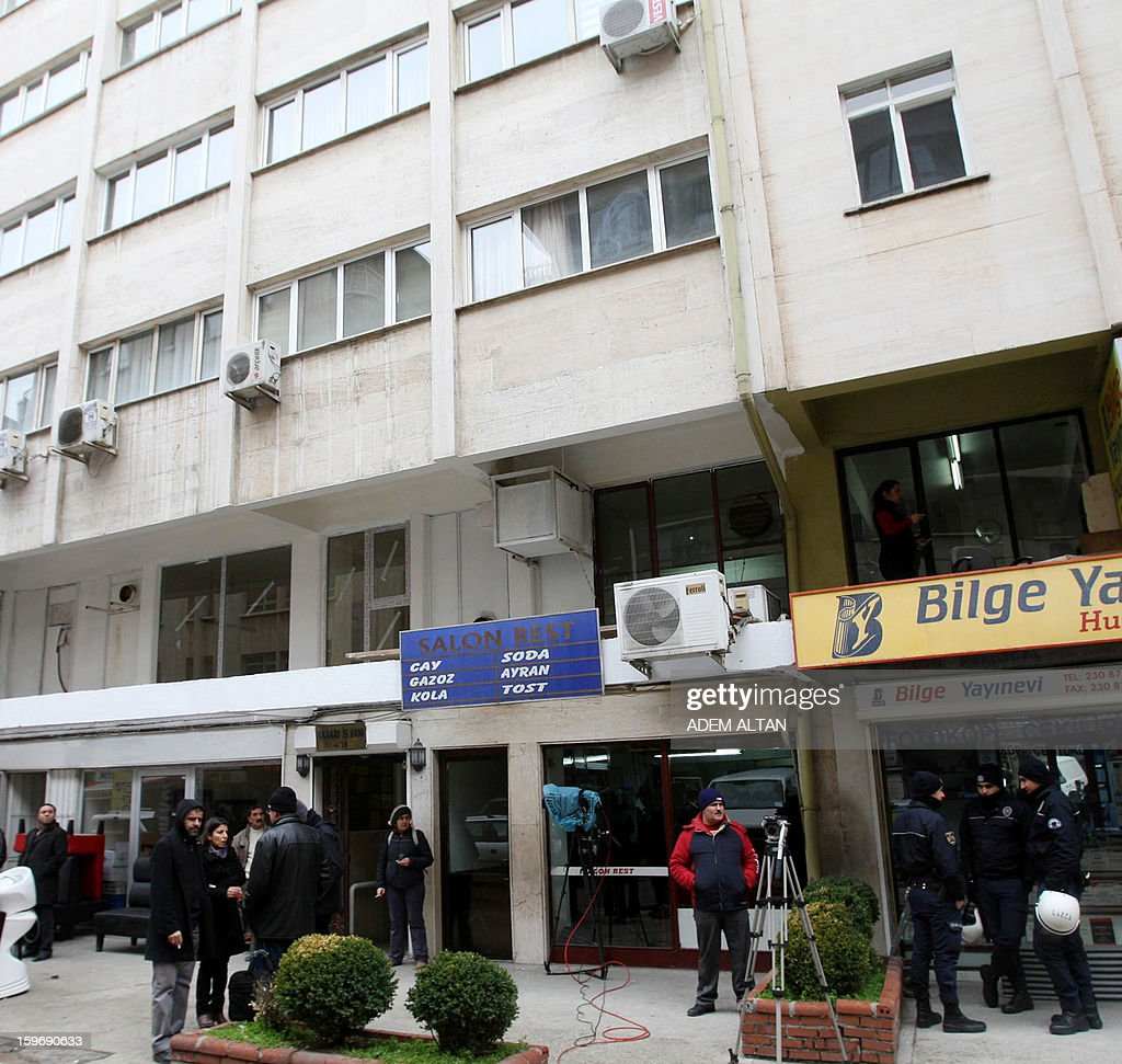 People and security members stand outside the Conpemporary Lawyers' Association during a police search inside the building on January 18, 2013 in Ankara