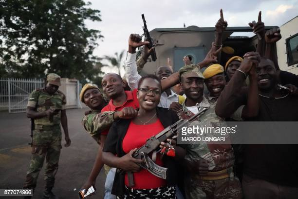 TOPSHOT People and soldiers celebrate after the resignation of Zimbabwe's president on November 21 2017 in Harare Car horns blared and cheering...